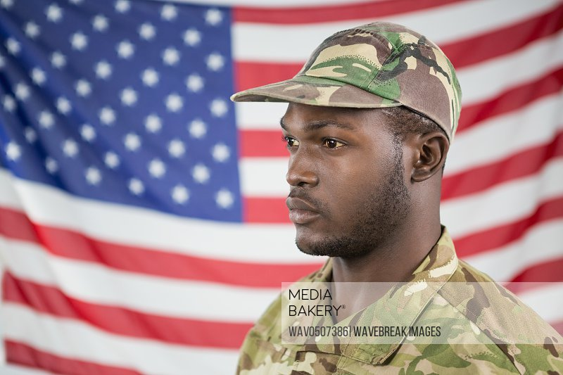 Close- up of soldier standing against american flag