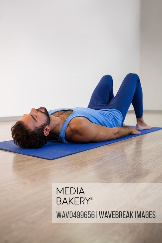 Man performing yoga exercise in fitness studio