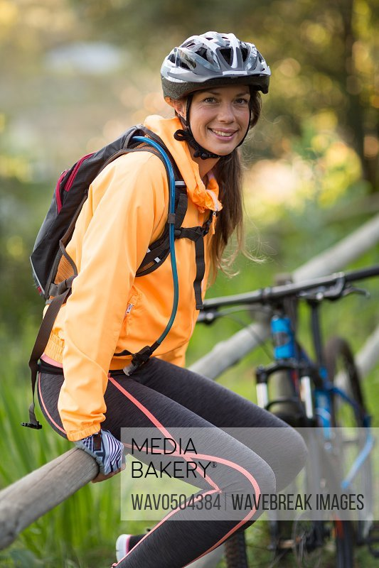 Female biker sitting on a fence in countryside forest