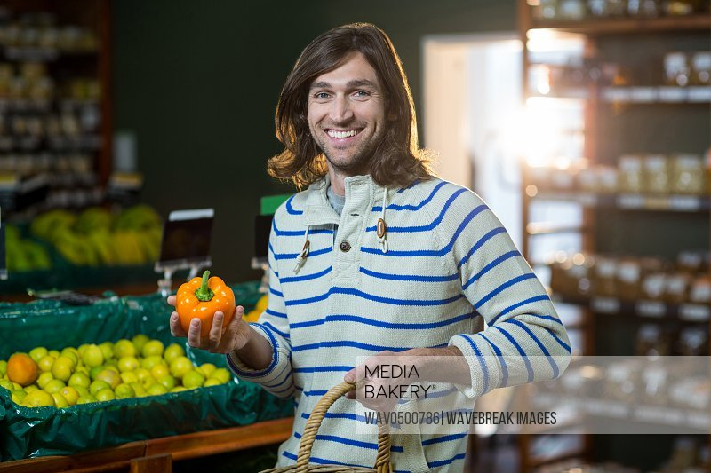Portrait of man with a basket selecting bell pepper in organic section of supermarket