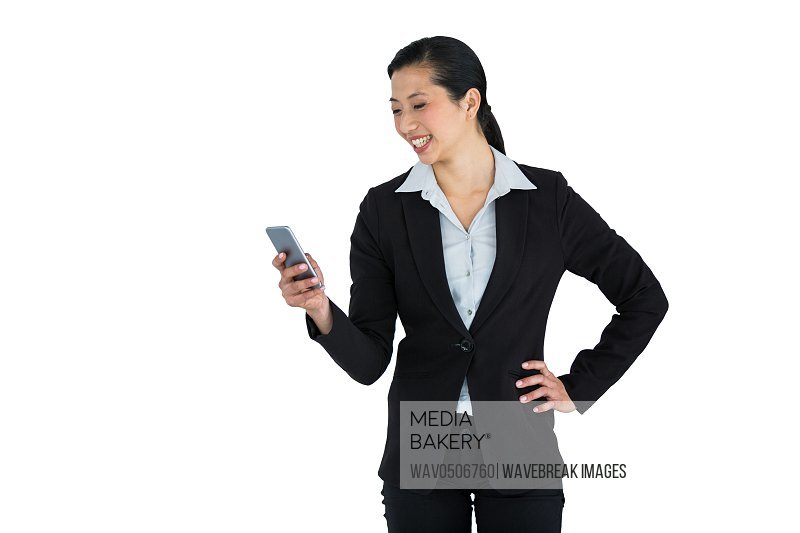Smiling businesswoman using mobile phone against white background