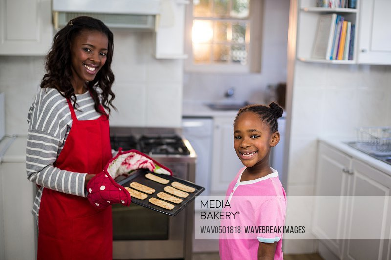 Mother and daughter with a baking tray in kitchen