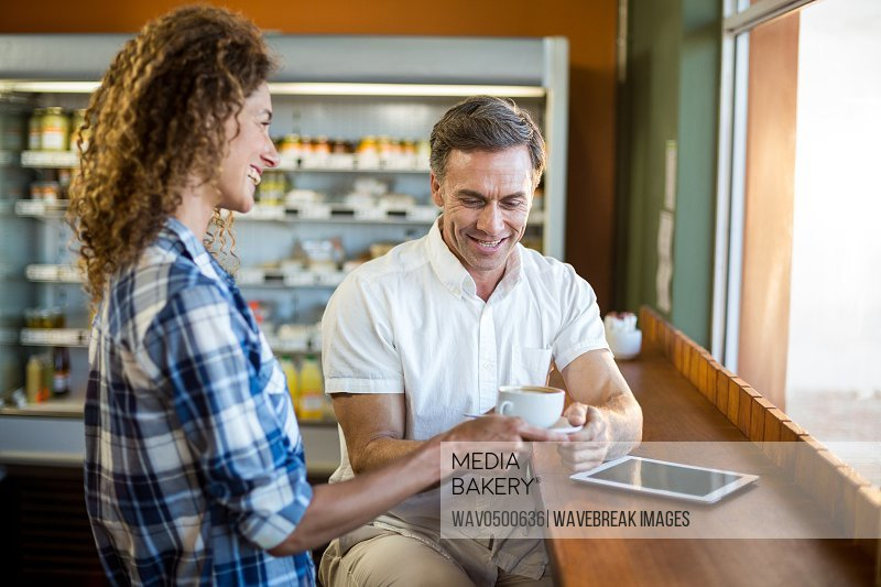 Smiling woman offering a cup of coffee to man in cafe