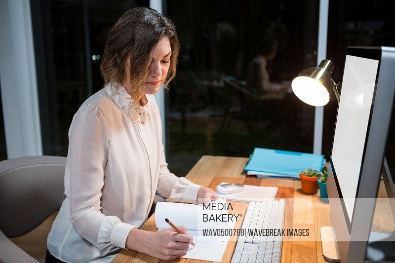 Businesswoman writing on paper at her desk in the office