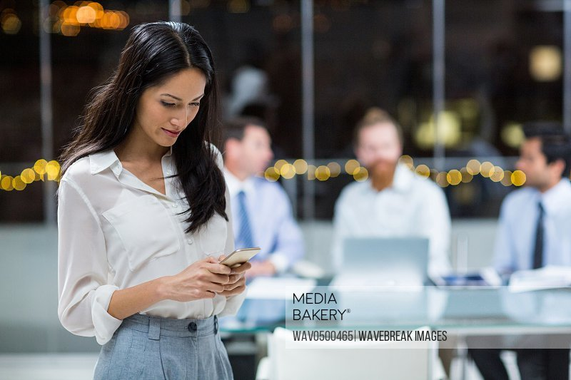 Businesswoman text messaging on mobile phone in the office