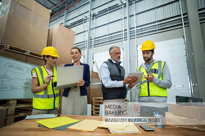 Warehouse managers and workers discussing with laptop and digital tablet in warehouse
