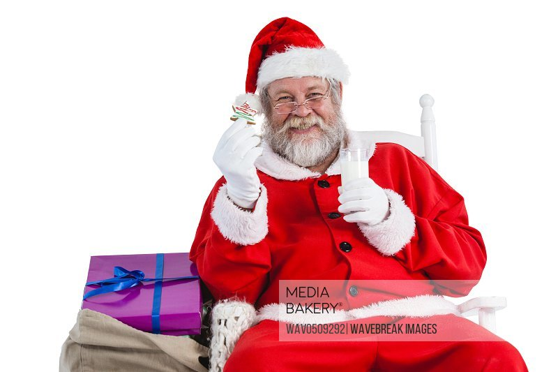 Santa claus having a glass of milk and cookies