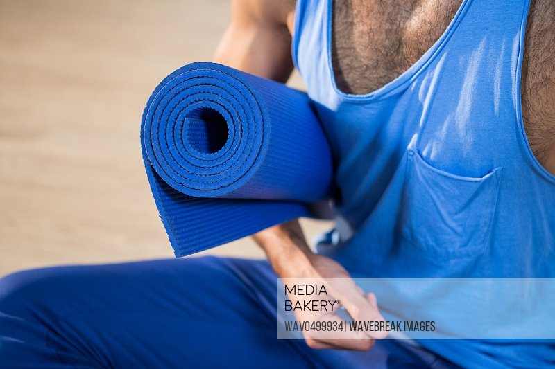 Mid section of man holding exercise mat in gym