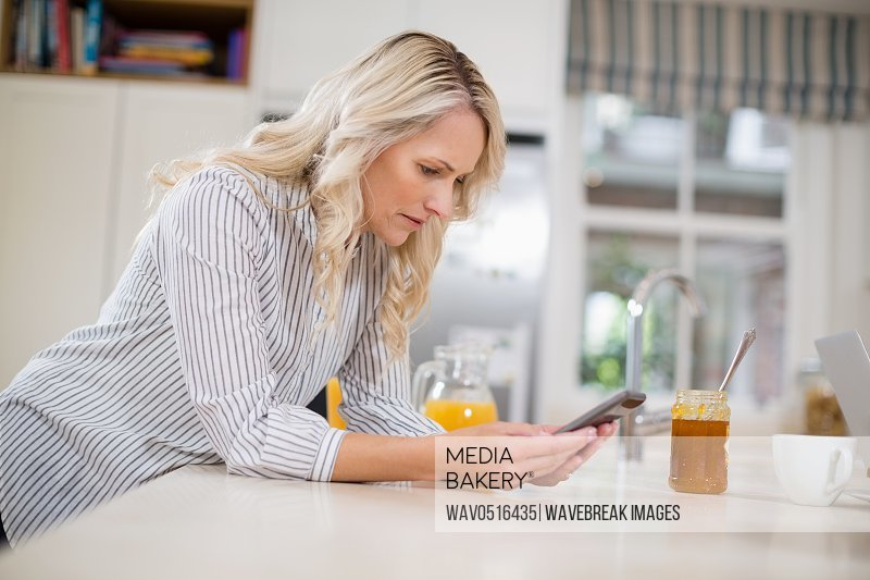 Beautiful woman using mobile phone in kitchen