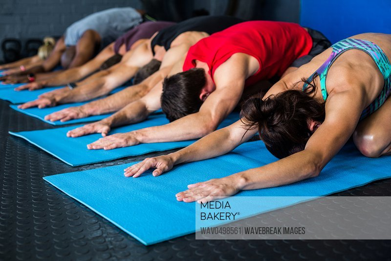 Athlete friends stretching while kneeling in gym
