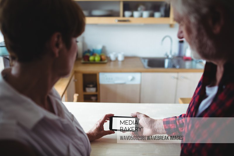 Senior couple using mobile phone in kitchen