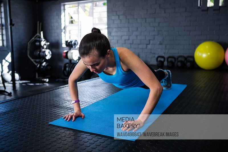 Sporty young woman doing push-ups in gym