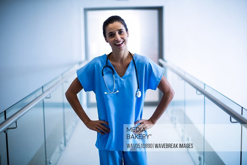 Portrait of female surgeon standing with hands on hip at hospital