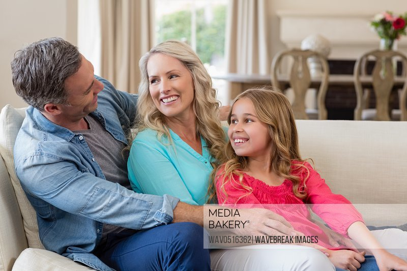 Parents and daughter having fun in living room