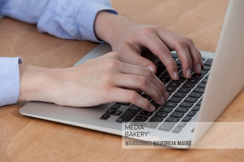 Businesswoman sitting at desk and using laptop