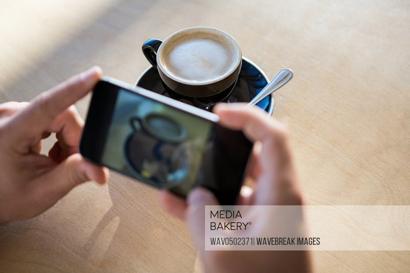 Female hands photographing a coffee cup in the coffee shop