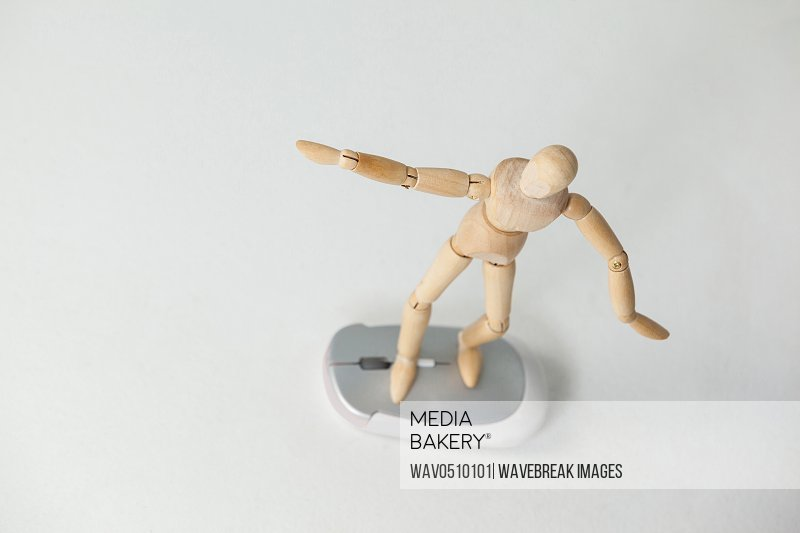 Wooden figurine standing with arms spread on a mouse against white background