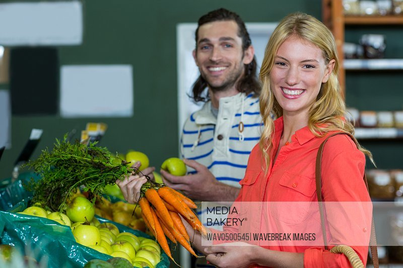 Happy couple selecting fruits and carrots in organic section of supermarket