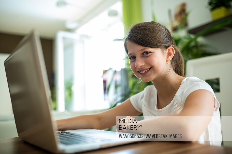 Portrait of smiling girl with laptop in the living room at home