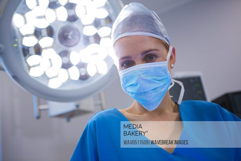 Portrait of female surgeon wearing surgical mask in operation theater at hospital