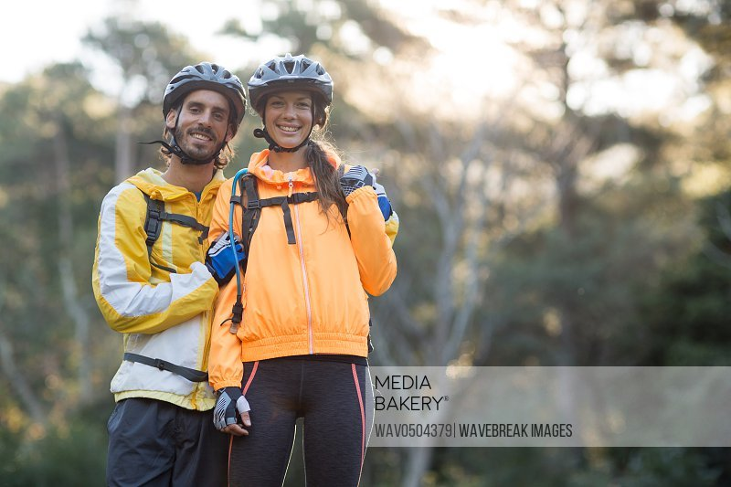 Portrait of biker couple standing in countryside forest