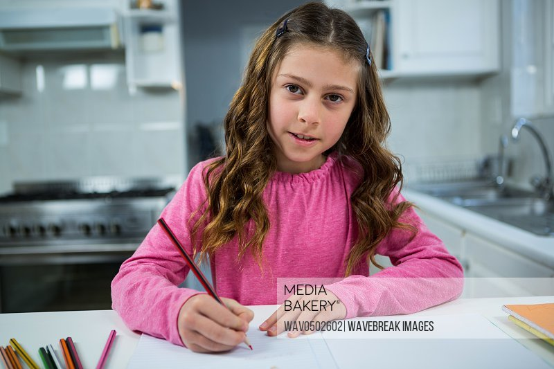Portrait of girl doing her homework at home in the kitchen