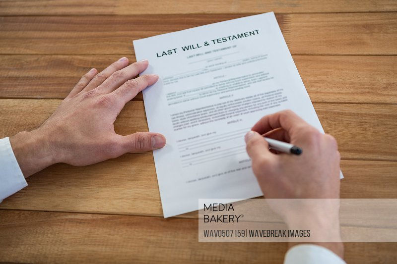 Businessman filling last will and testament form in office