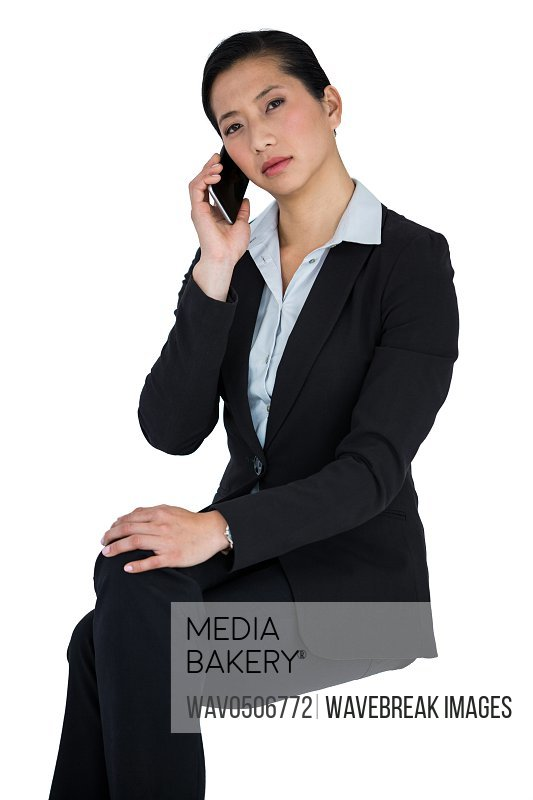 Portrait of businesswoman talking on mobile phone against white background