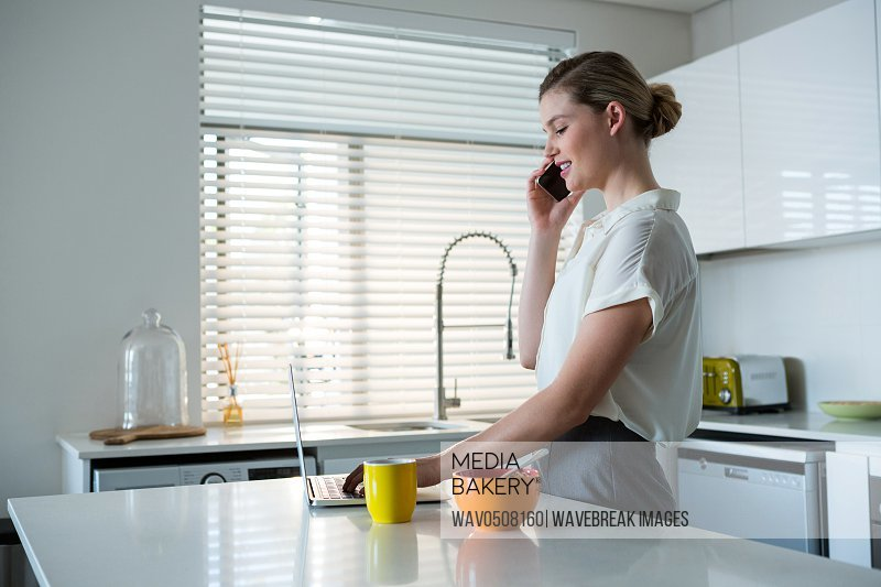 Woman talking on mobile phone while using laptop in kitchen at home