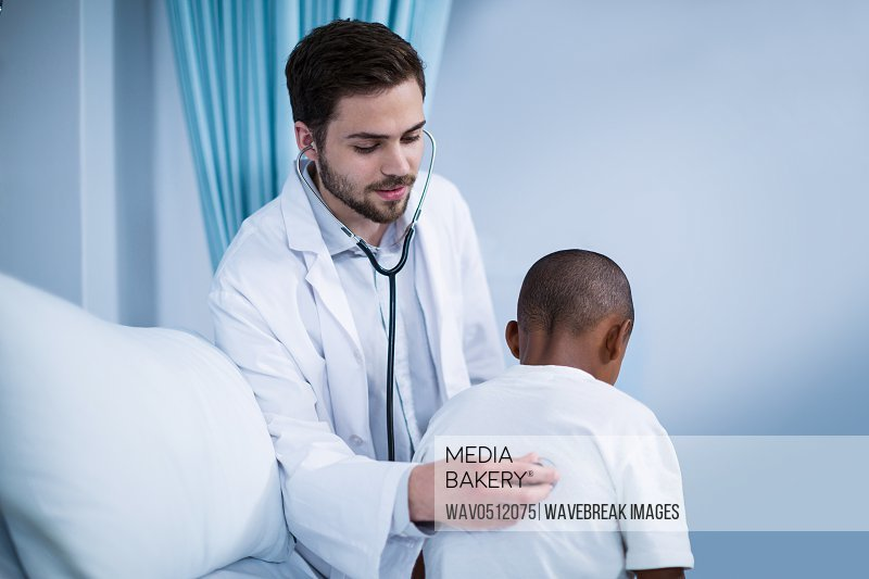 Doctor examining a child with stethoscope in hospital