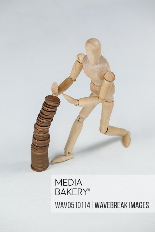Wooden figurine preventing stack of coins from falling against white background