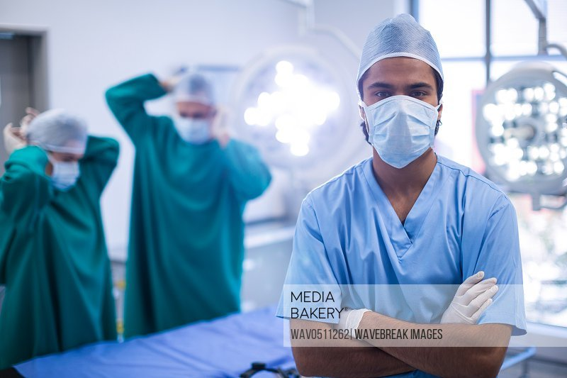 Portrait of surgeon standing with arms crossed in operation room at hospital