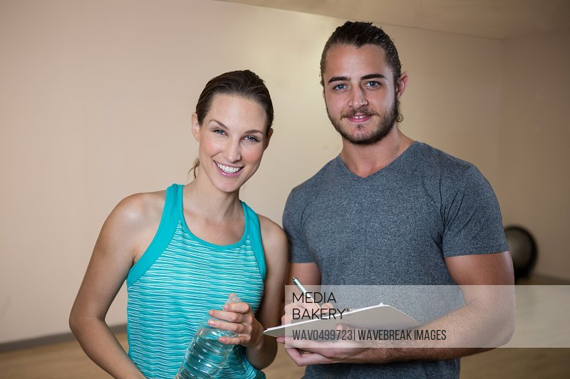 Portrait of smiling fitness trainer and woman in fitness studio