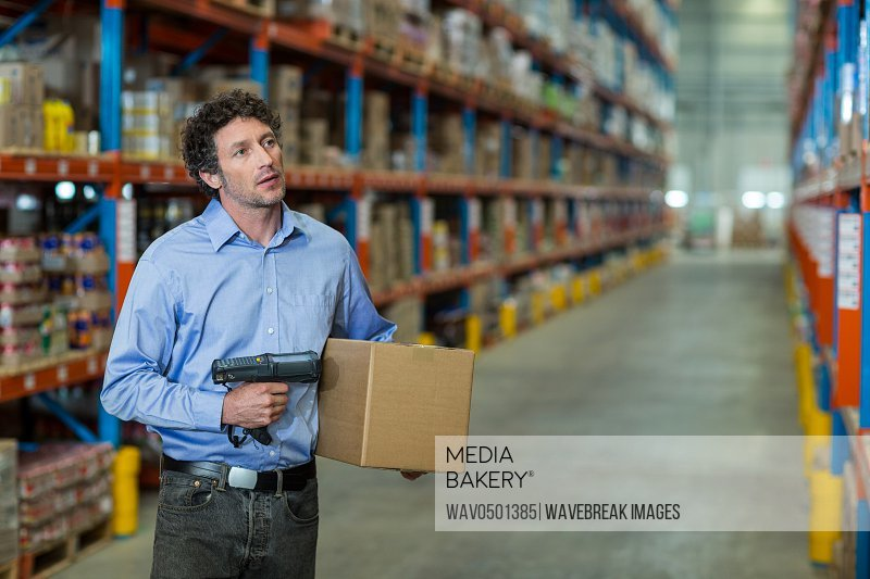 Warehouse worker holding cardboard box and barcode scanner machine in warehouse