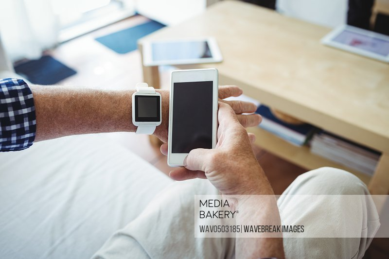 Mid section of senior man using mobile phone at home