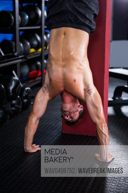 Shirtless athlete doing handstand in gym