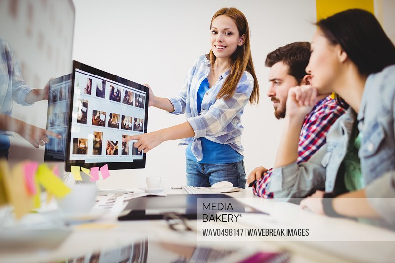 Portrait of smiling businesswoman showing computer screen to coworkers in creative office