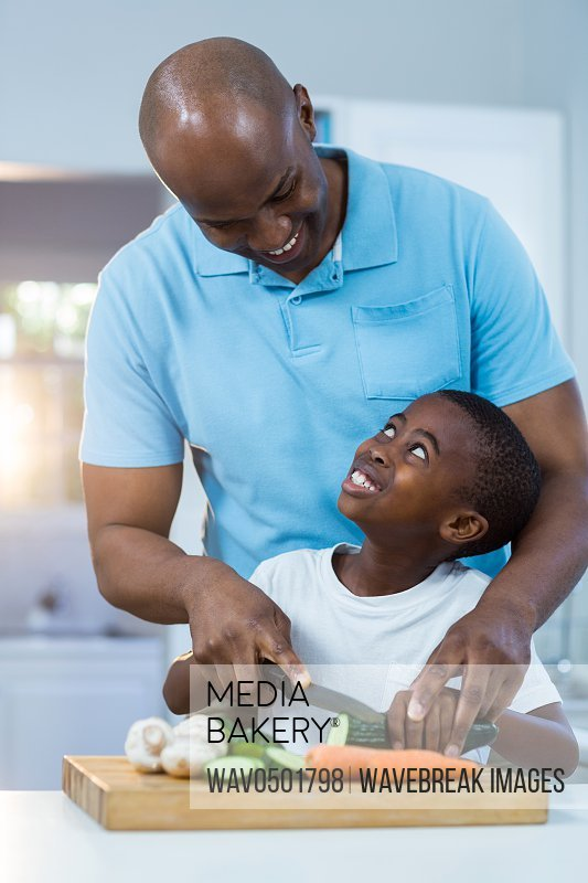 Father and son preparing food in kitchen