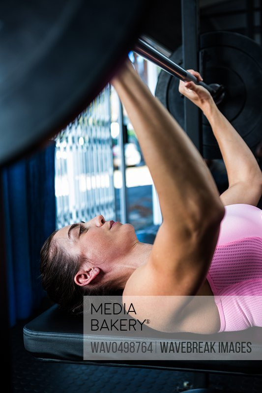 Side view of athlete holding barbell while lying on bench press in gym
