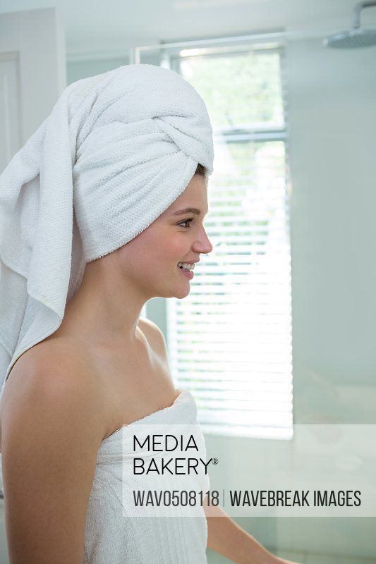 Woman in a bathrobe with a towel on her head at bathroom