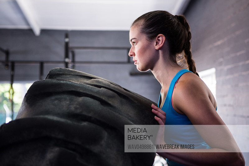 Side view of female athlete pushing tire while exercising in gym