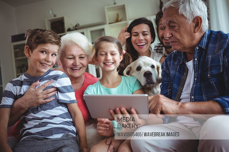 Happy multi-generation family using digital tablet in living room at home