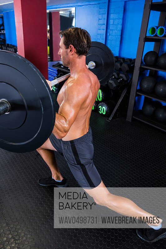 Male athlete holding barbell in gym