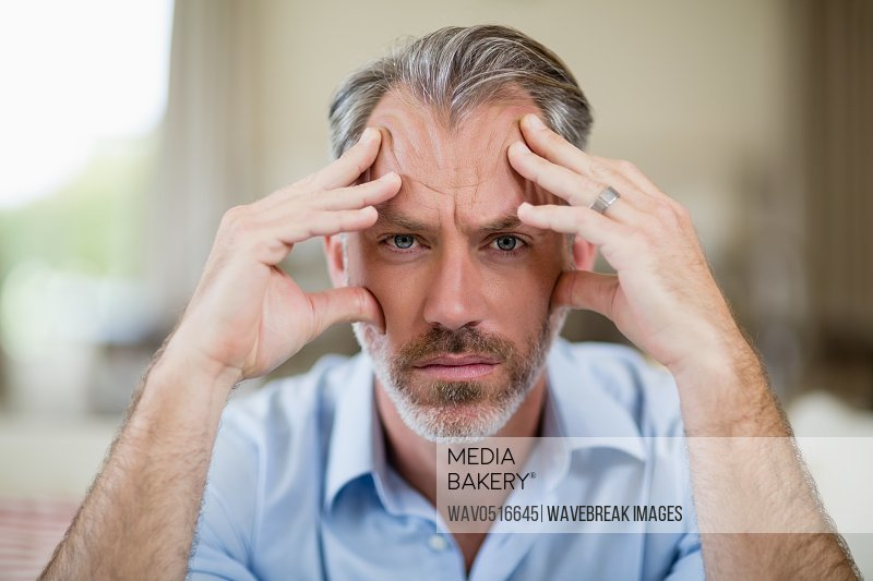 Tense man with hand on forehead sitting on sofa in living room