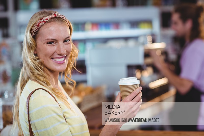 Portrait of smiling woman holding cup of coffee in cafA?
