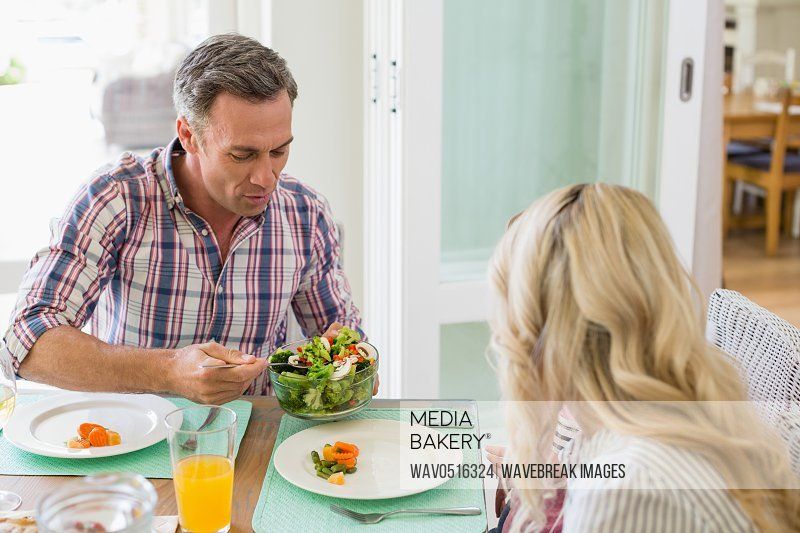 Man serving food to woman on dinning table