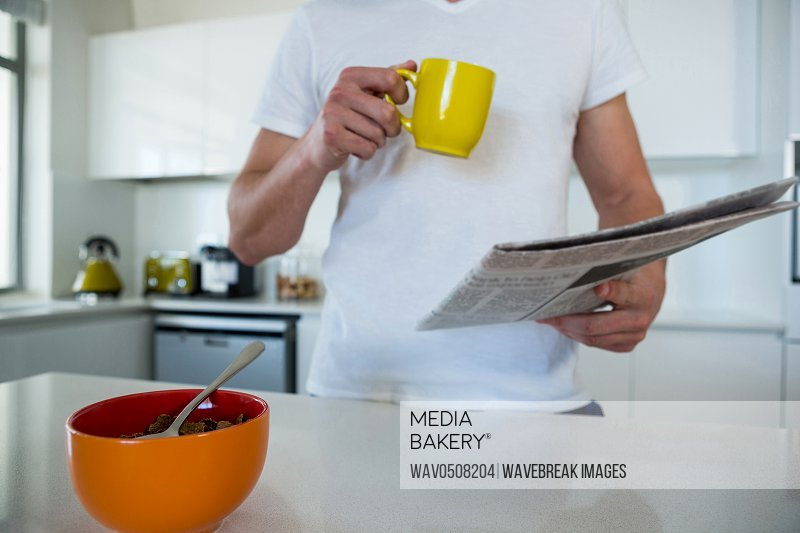 Mid section of man reading newspaper while having coffee in kitchen at home