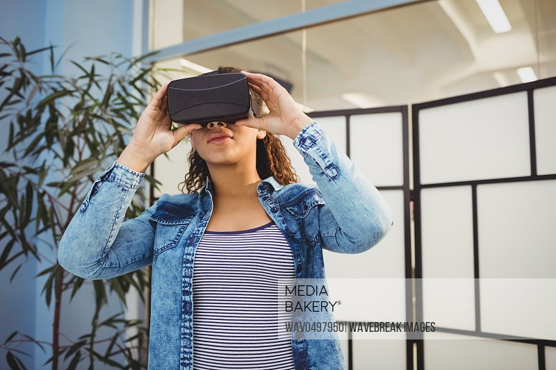 Low angle view of young female executive enjoying virtual reality headset at creative office