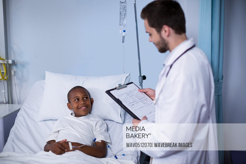 Doctor reading report while patient sleeping on bed in hospital