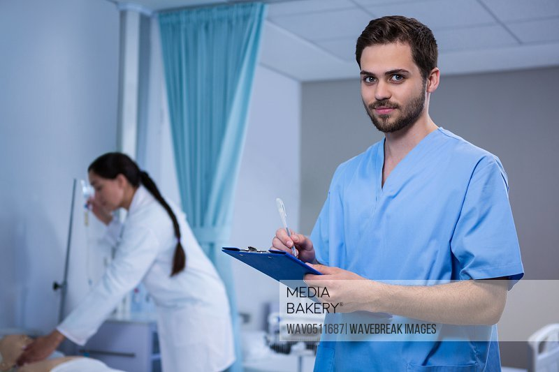 Portrait of doctor writing on clipboard in hospital